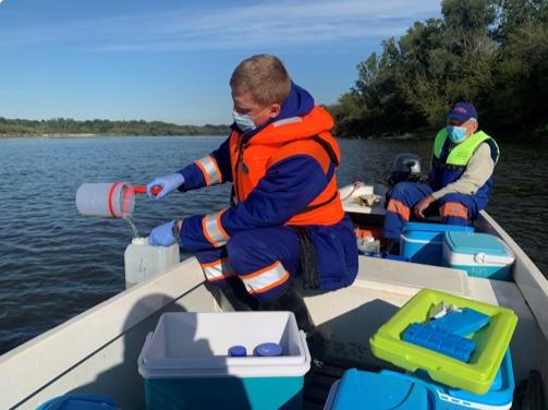 Pracownicy MPWiK pobierają wodę do badań z łodzi